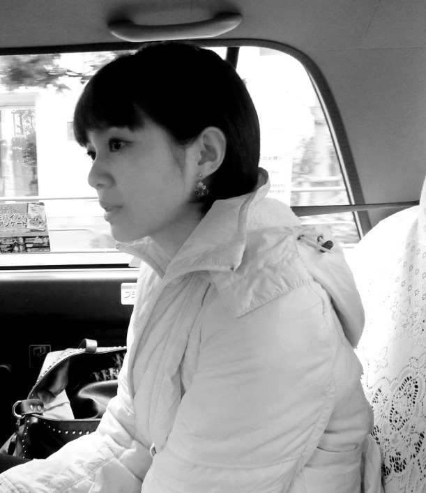 Me with short hair and blunt bangs, all wrapped in sweater sitting in a taxi in Tokyo.
