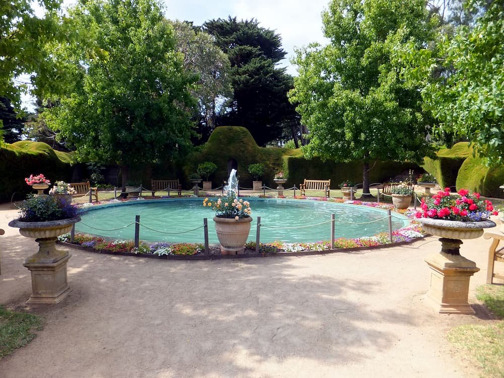 Garden with a fountain surrounded by a ring of flowerbed and pots of flowers.