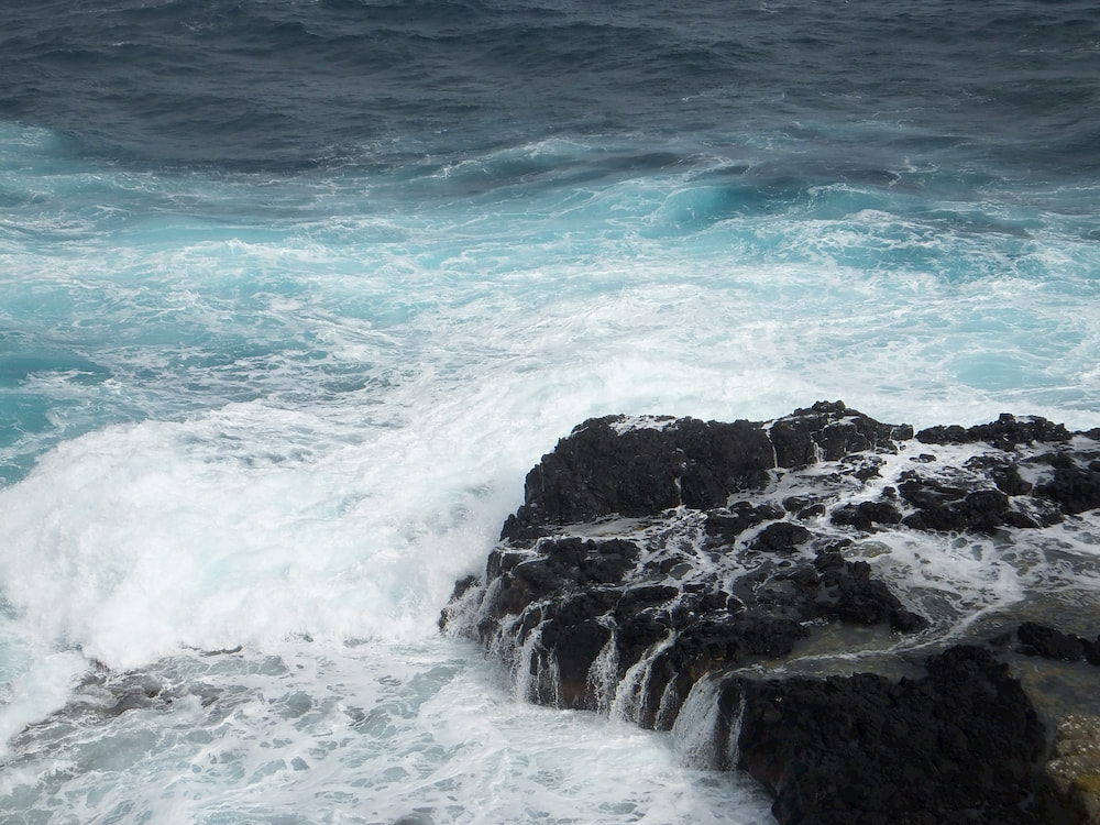 Close up of the turquoise waves hitting the dark rocks.