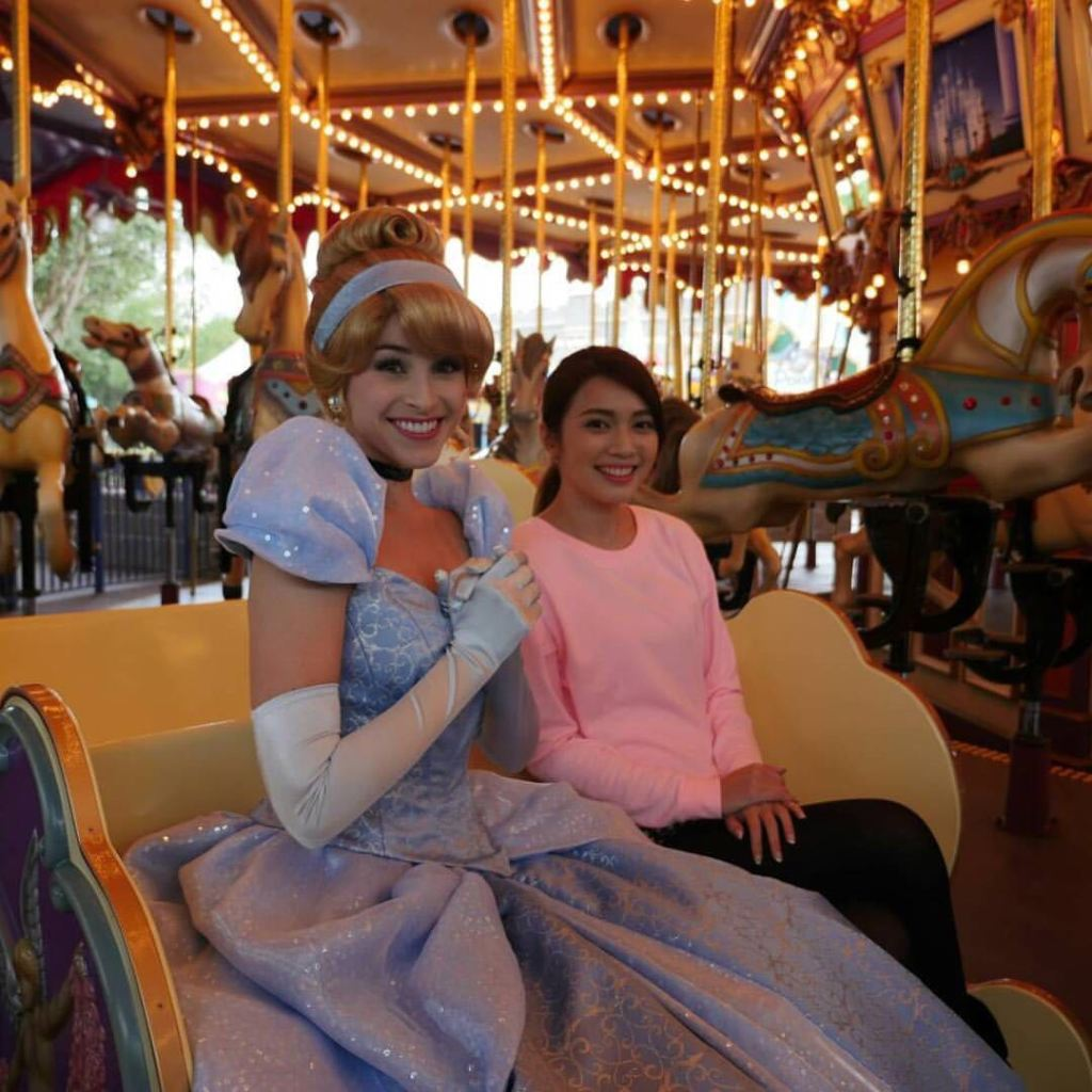 Me sitting next to Cinderella on a carriage in the carousel.