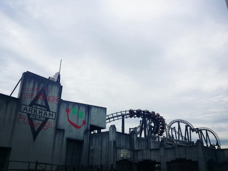 "Arkham Asylum is presented as a grey building defaced with graffiti ""Welcome to The Joker's Funhouse!"". The rollercoaster track winds in several inversions behind the building."