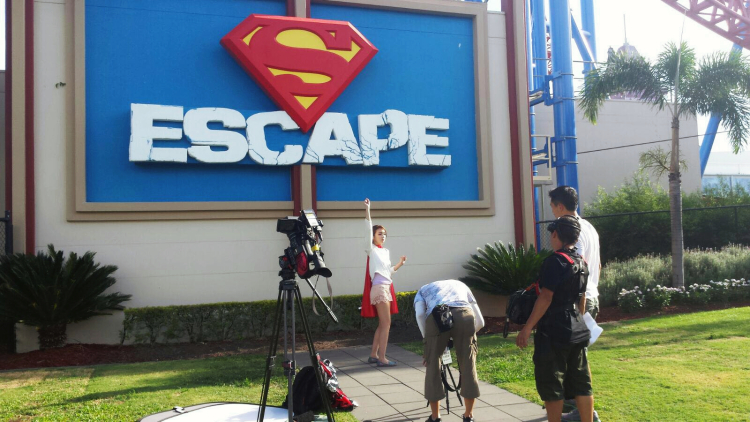 Me wearing a Superman cape in front of Superman Escape raising my right arm in a fake attempt to fly.