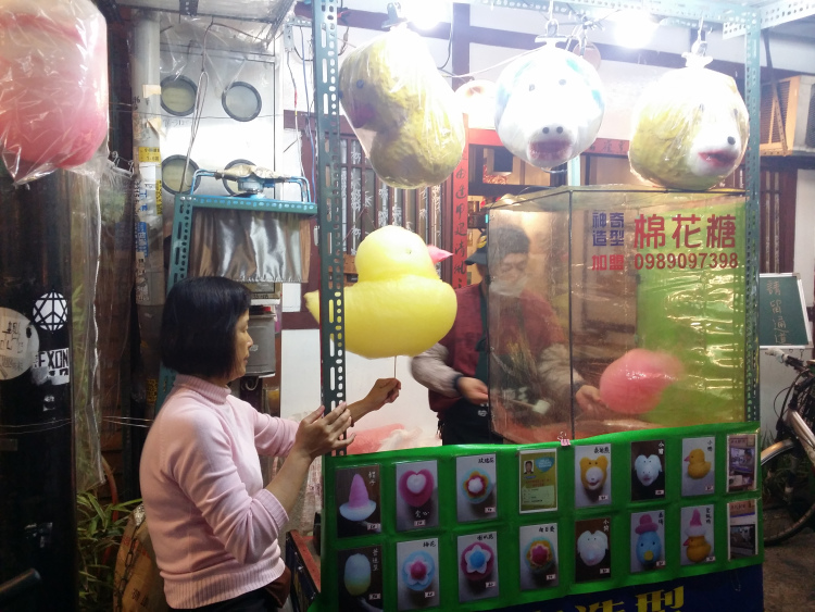 Woman holding a yellow duck-shaped cotton candy at the cotton candy stall while a man makes a pink cotton candy.