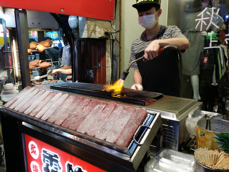 Young man grilling a large slab of beef.