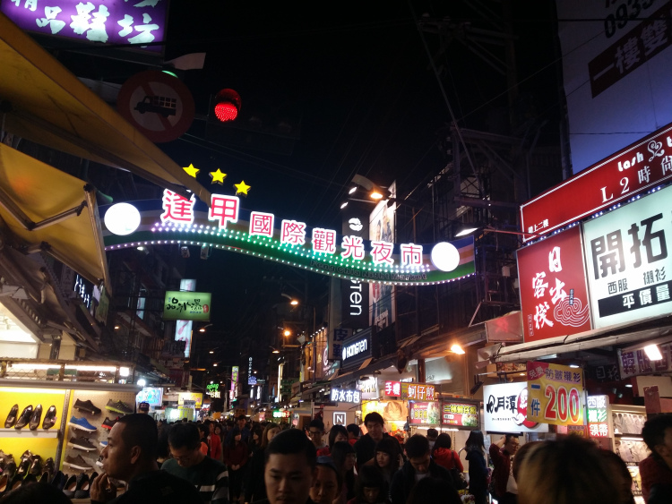 Crowded Fengjia Night Market at night.