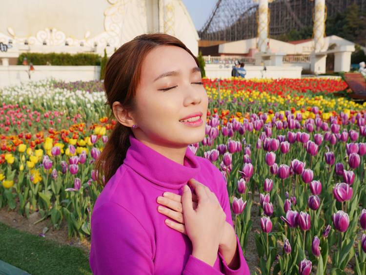 Placing my hands over my chest to feel the breeze, with a backdrop of colourful tulips and T-Express behind.