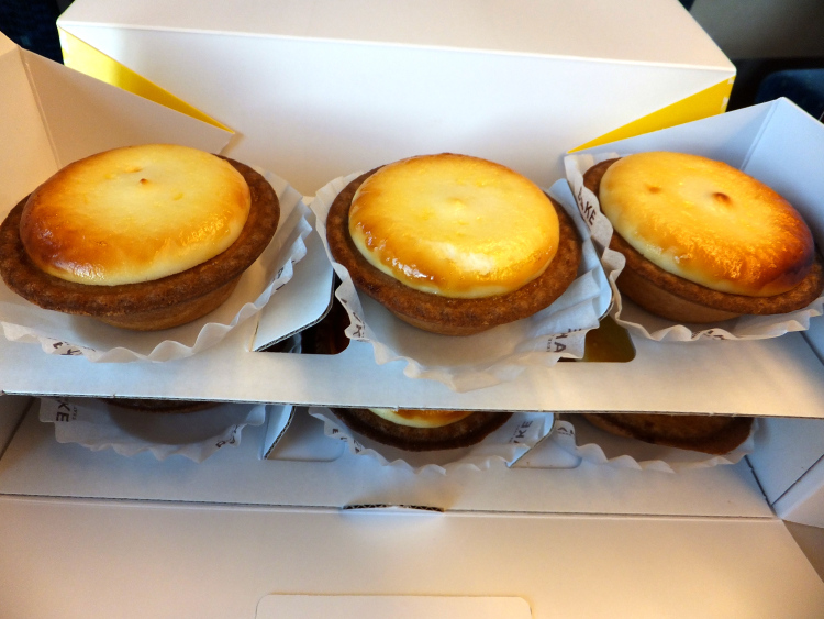 Six pieces of BAKE cheese tarts arranged in rows of three over each other in an open box.