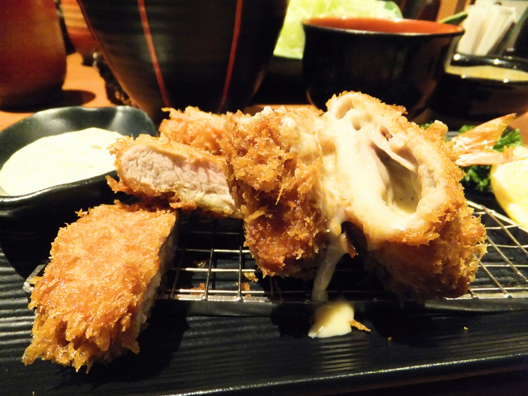 Cheesy tonkatsu served in a black plate.
