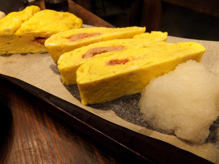 Cut slices of tamagoyaki stuffed with mentaiko arranged in a row on a plate.