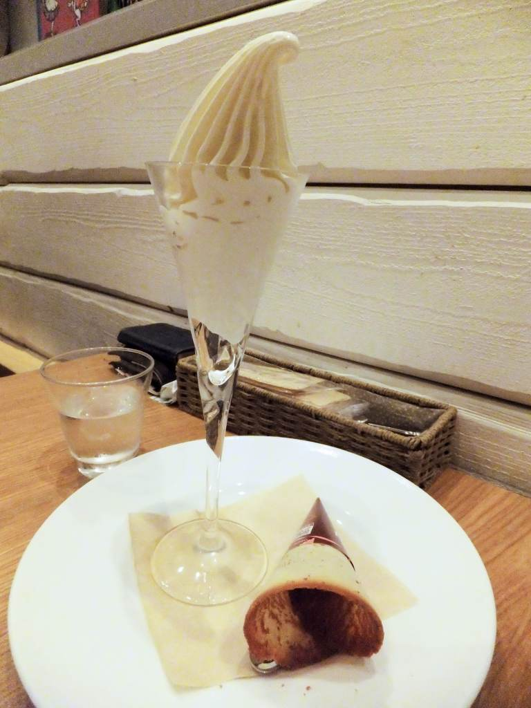 Creme soft-serve in a glass with the wafer cone by the side on a white plate.