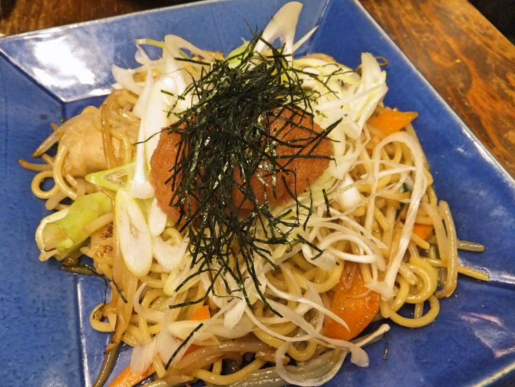 Yakisoba served in a blue plate topped with mentaiko and thinly shredded seaweed.