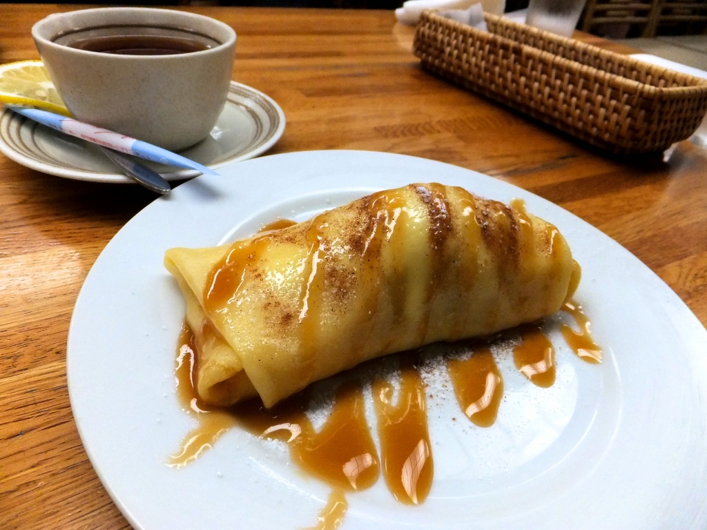 Baked apple crepe drizzled with cinnamon sauce served on a white plate, with a cup of tea on the side.