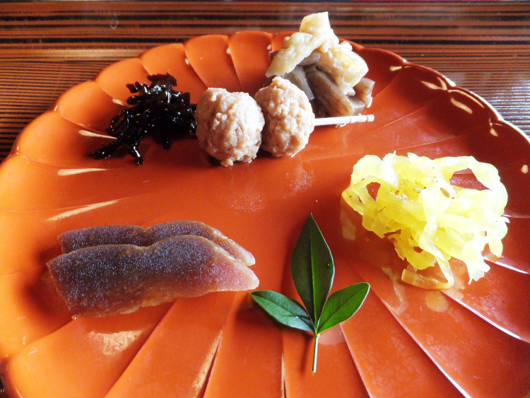 Side dishes arranged delicately on a scalloped orange plate.