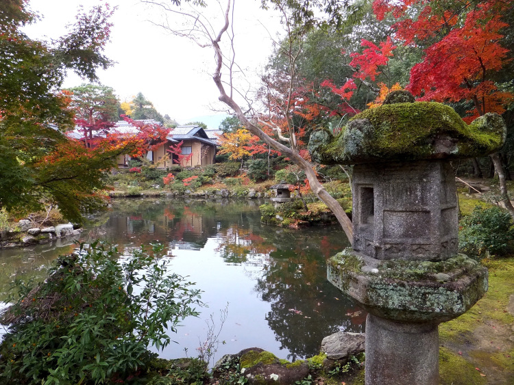 A moss-covered stone lamp in front of a pond in Isuien Garden surrounded by autumn foliage.