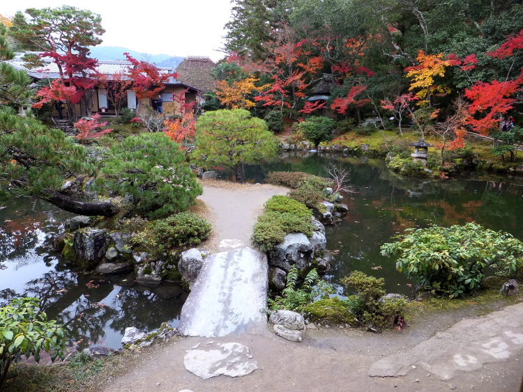 Isuien Garden pond surrounded by red and yellow autumn foliage.