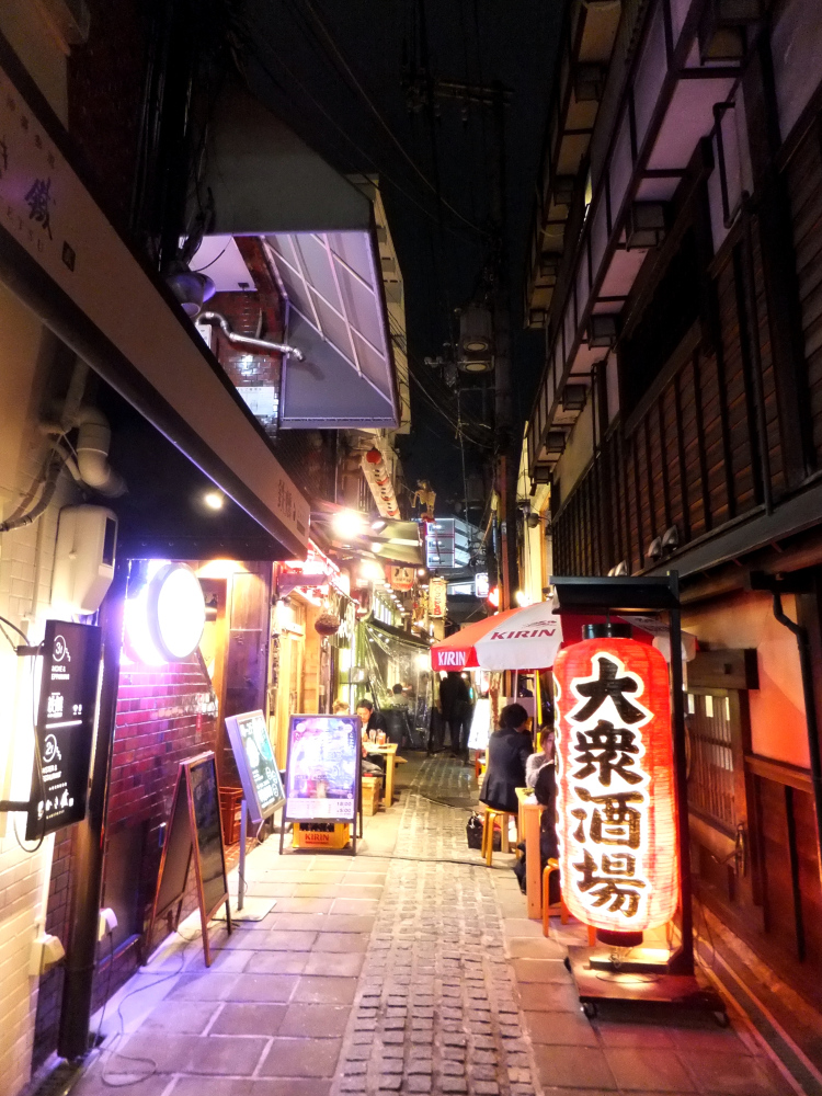 An brightly lit alleyway filled with izakaya shops.