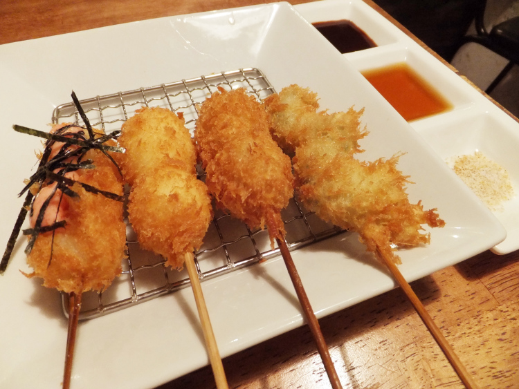 Four sticks of kushikatsu on a plate, with a side of dipping in three flavours - dark sauce, ponzu sauce and salt.
