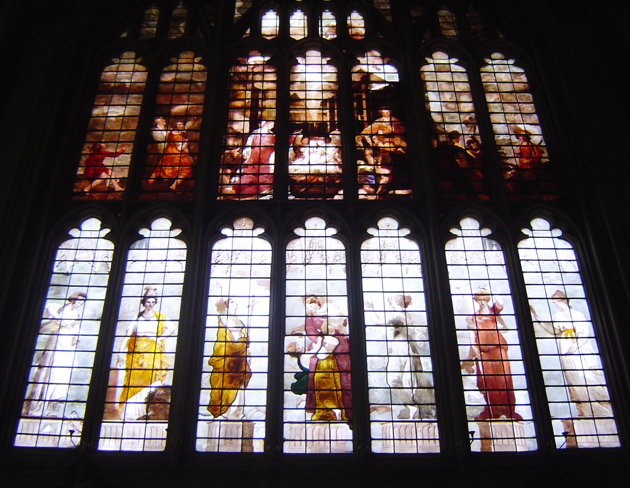 A large stained glass windows with biblical paintings.