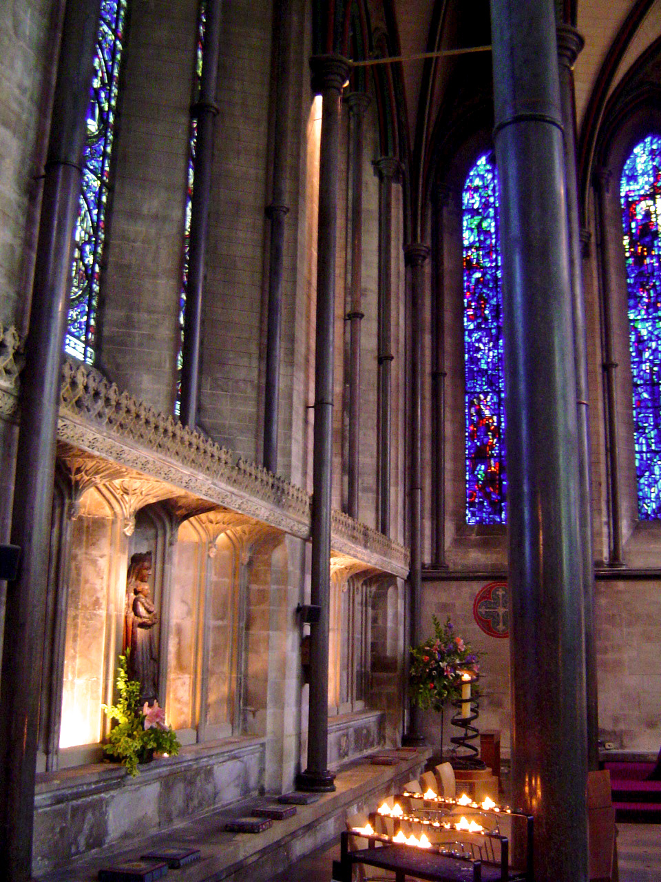 Lit candles glowing softly in a cathedral with blue stained glass windows.