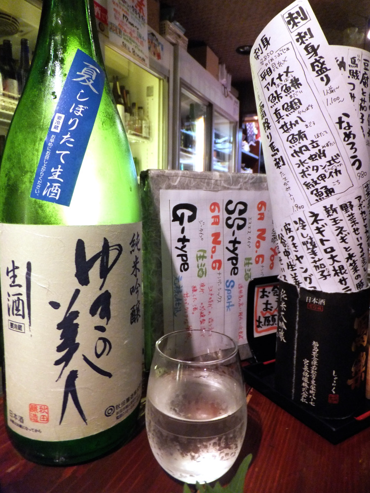 A small clear glass of sake between a large green bottle of sake and a menu written in Japanese stuffed in a black box.