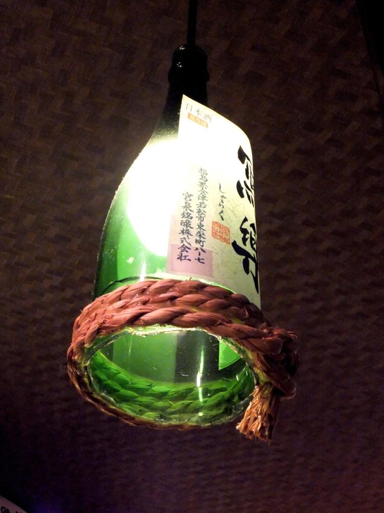 A green sake bottle repurposed as a hanging lamp.