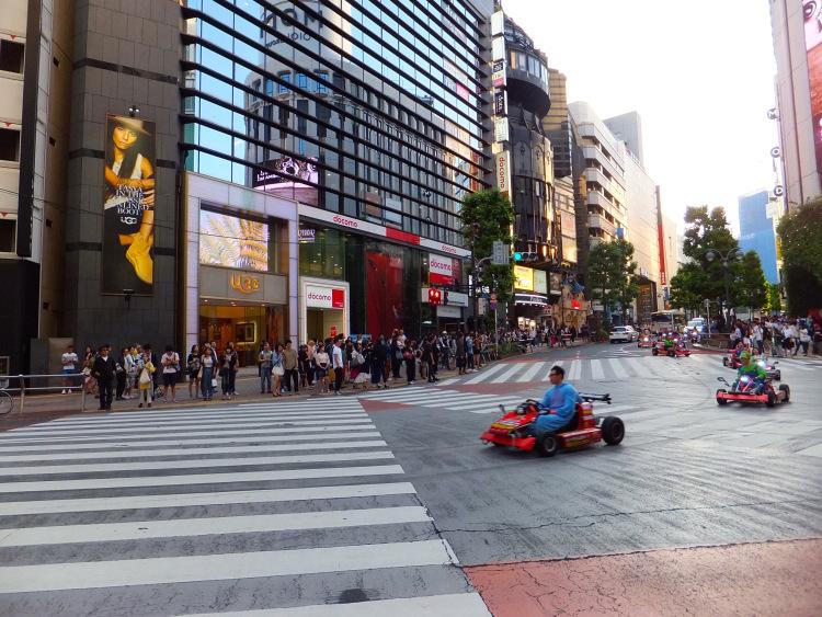 Mario karts racing across the road in Shibuya.