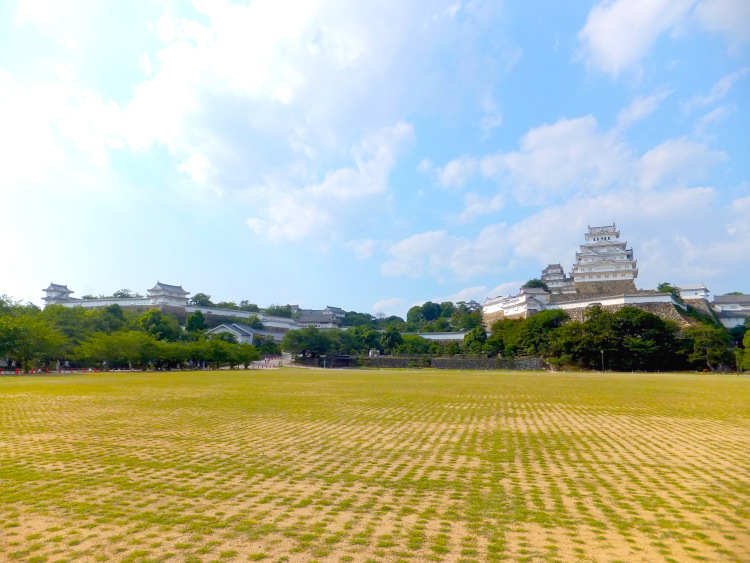 A wide view of Himeji Castle against a blue sky with scattered white clouds.