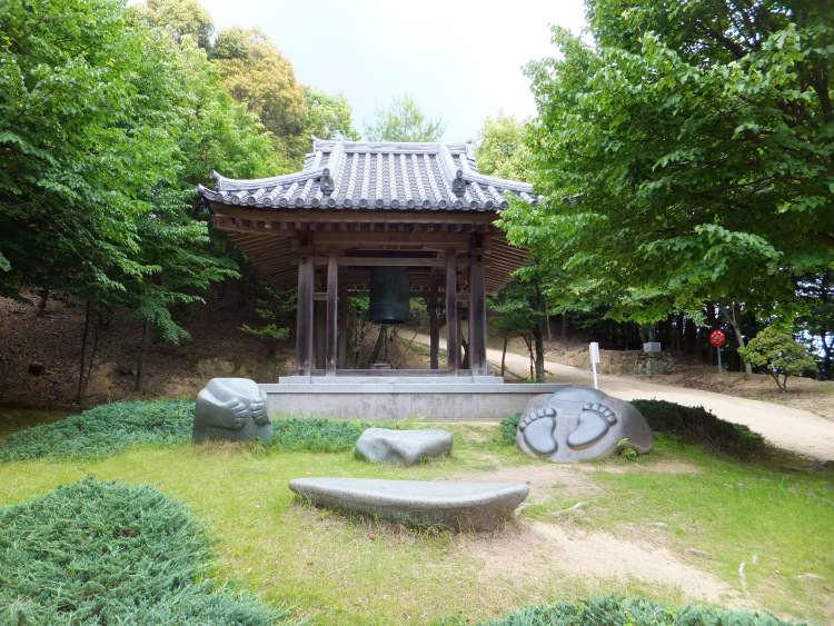 A little pavilion in the forest clearing housing a large iron bell with some sculpted rocks in front.
