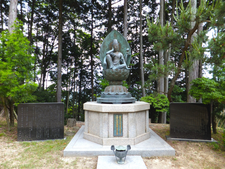 An iron kannon statue sitting on a lotus leaf in the forest clearing.
