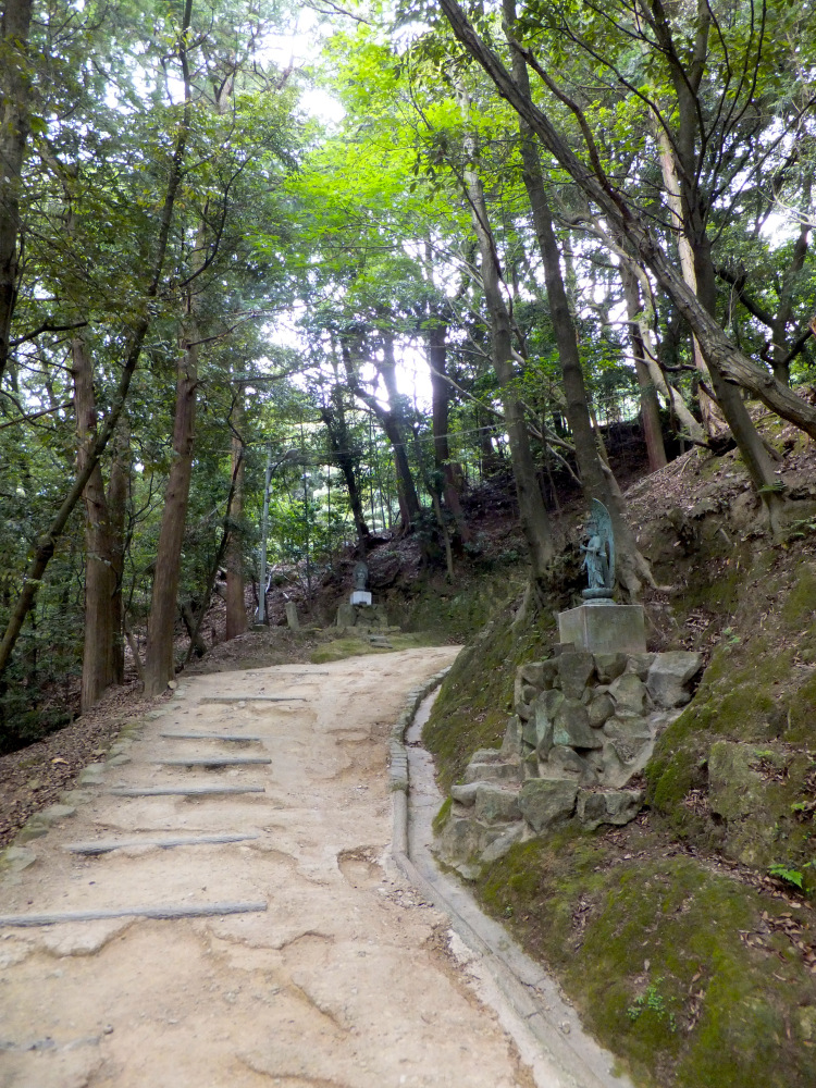 Little kannon statues lining the dirt path in the mountainous forest.
