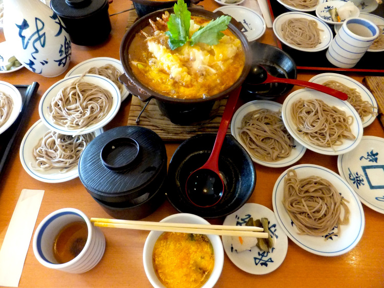 Shrimp tempura hotpot surrounded by several plates of sara soba.