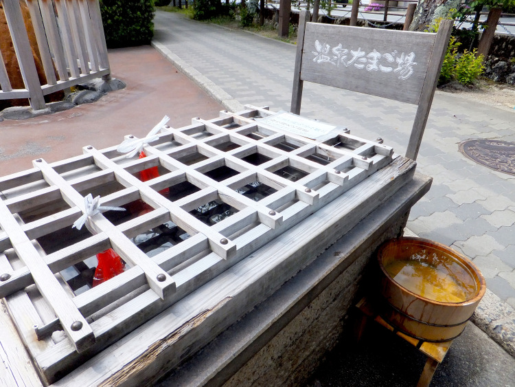 A large wooden box containing the hot spring water. Two bags of eggs bundled in red plastic netting tied to the wooden cover soak in the water.