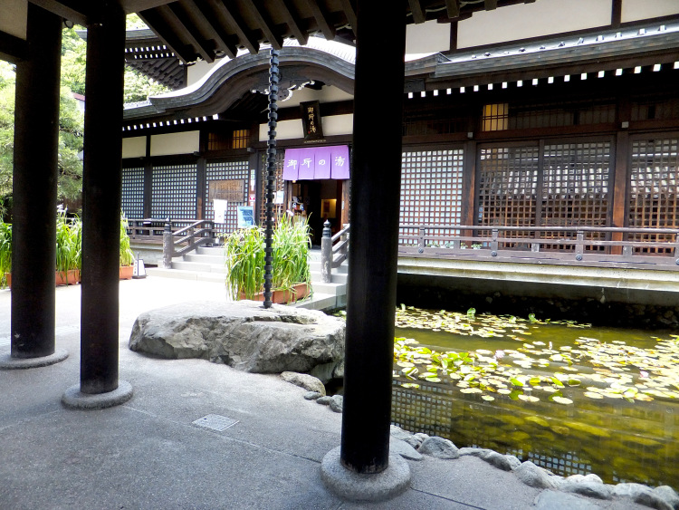 Entrance to Goshono-Yu surrounded by a pond filled with lotus leaves.