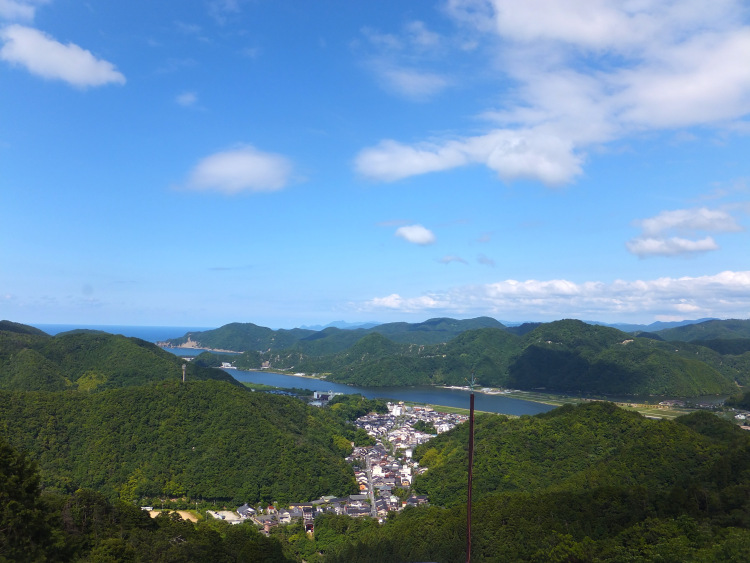 View of Kinosaki Onsen Town surrounded by green mountains and a calm river snaking into the deep blue sea under a clear blue sky.