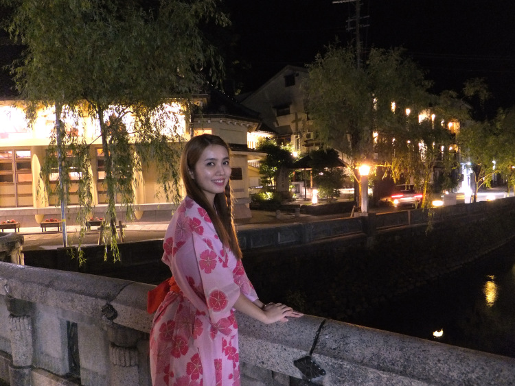 Me in the red and pink yukata standing on a stone bridge at night, with bathhouses fully lit in yellow lights behind, casting a golden glow on the weeping willow lining the street.