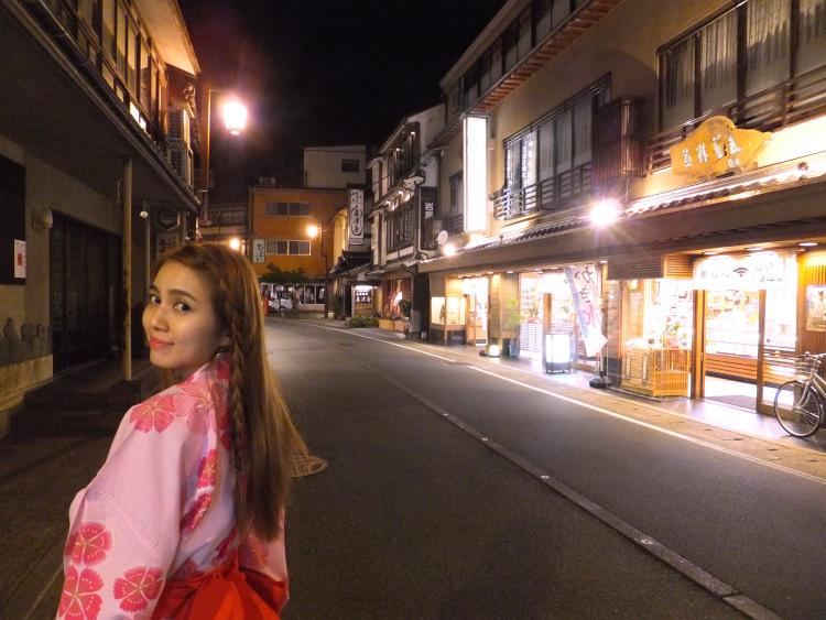 Me in the red and pink yukata walking along the illuminated street of Kinosaki Onsen Town at night.