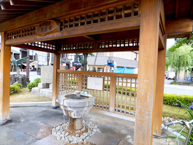 A stone drinking fountain under a wooden shelter at the entrance of Kinosaki Onsen Town.