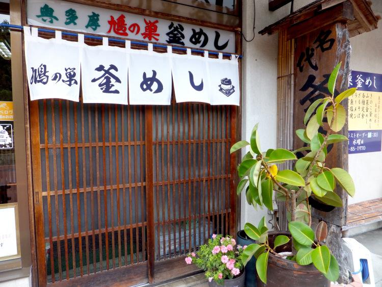 Wooden door with sign saying 鳩の巣釜めし.