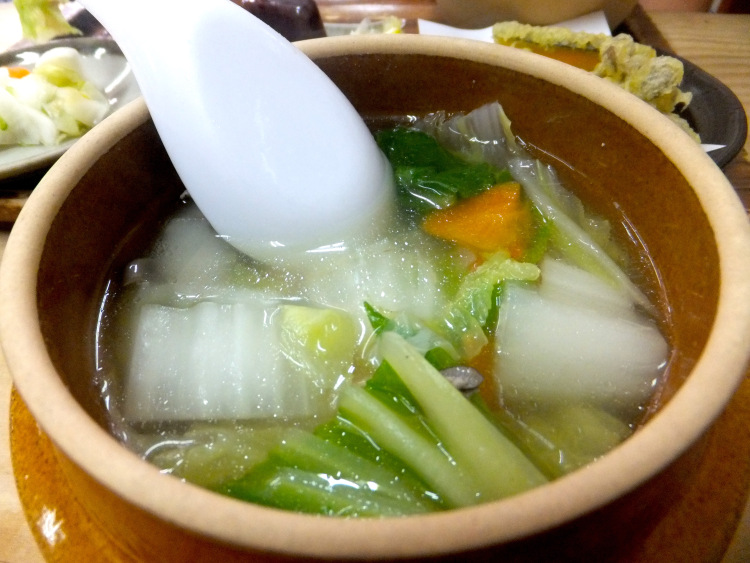 Clear soup in a brown claypot consisting of hakusai (napa cabbage), carrots and mushrooms.