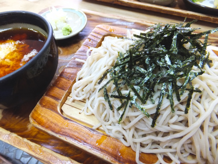 A plate of zaru soba served on a bamboo plate with tsuyu and other soba condiments by the side.