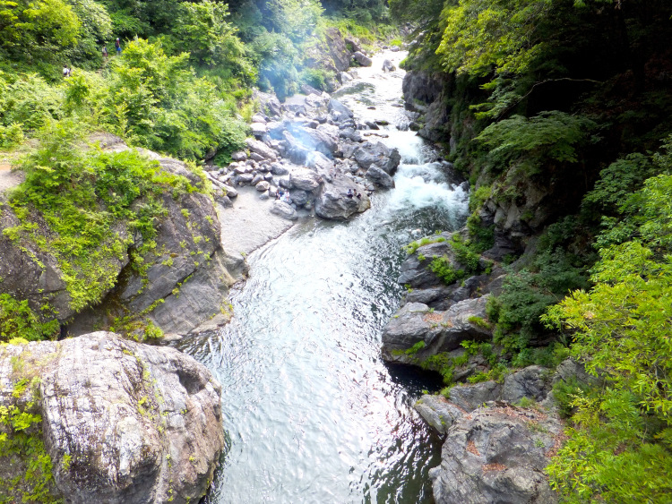 Bird's eye view of Hatonosu Ravine, with river water flowing and cutting through crags and rocks. From a distance, a group of people sit on the rocks barbecuing.