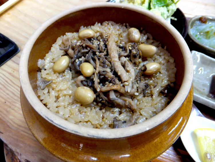 Rice in a brown claypot topped with peanuts and mushrooms.