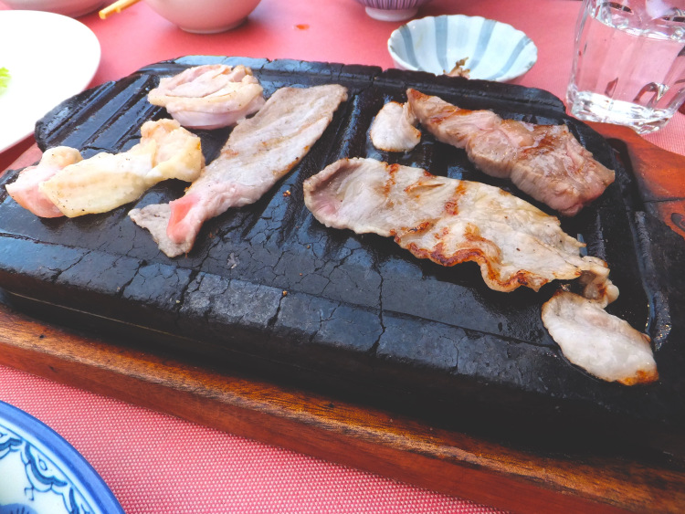 Meat cooking on a black stone grill.
