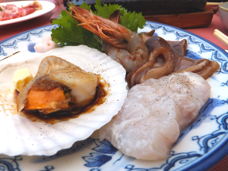 A plate of raw seafood - scallop, fish, squid and prawns, with a green garnish by the side.