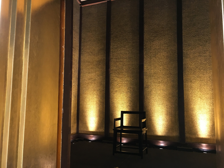 Golden walls surrounding a lone wooden chair.