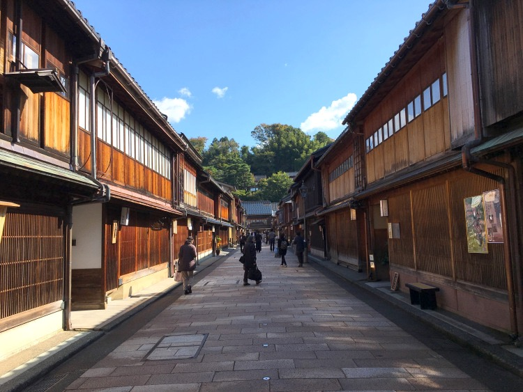 People walking in the teahouse district between rows of wooden houses.