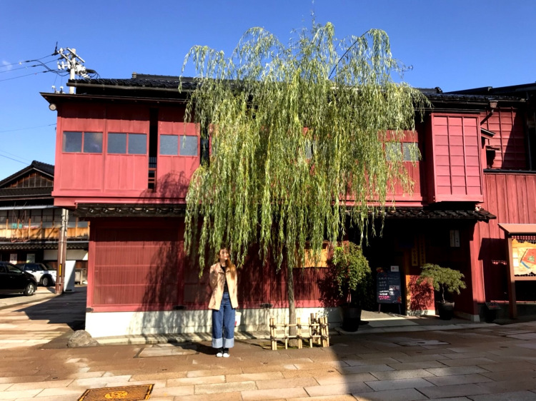 Me standing under a willow tree in front of a red wooden house.