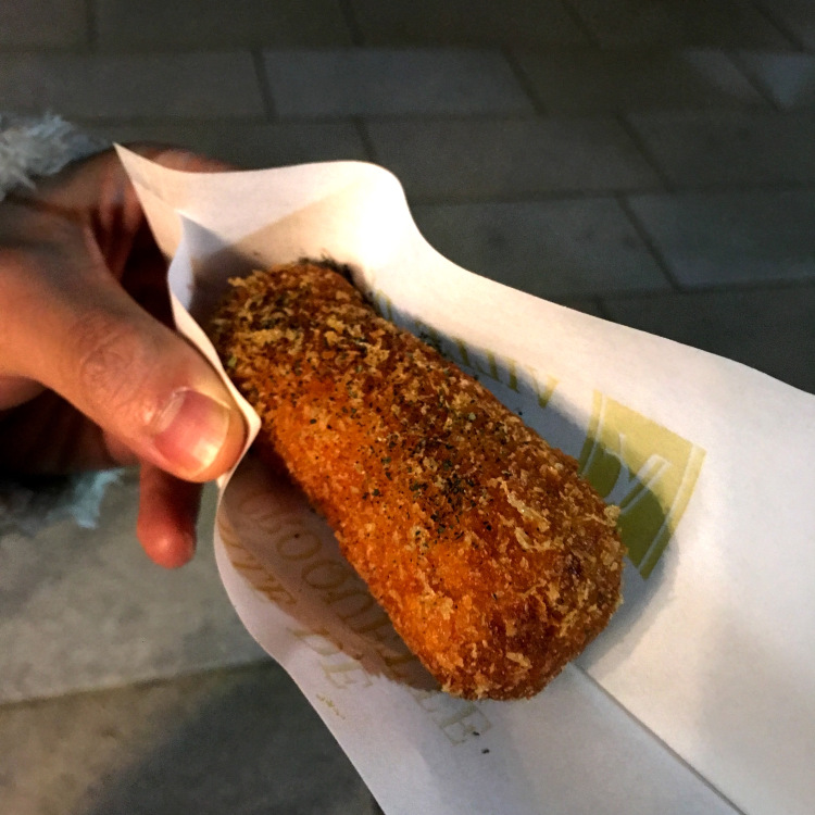 A long rectangular crispy korokke wrapped in paper.
