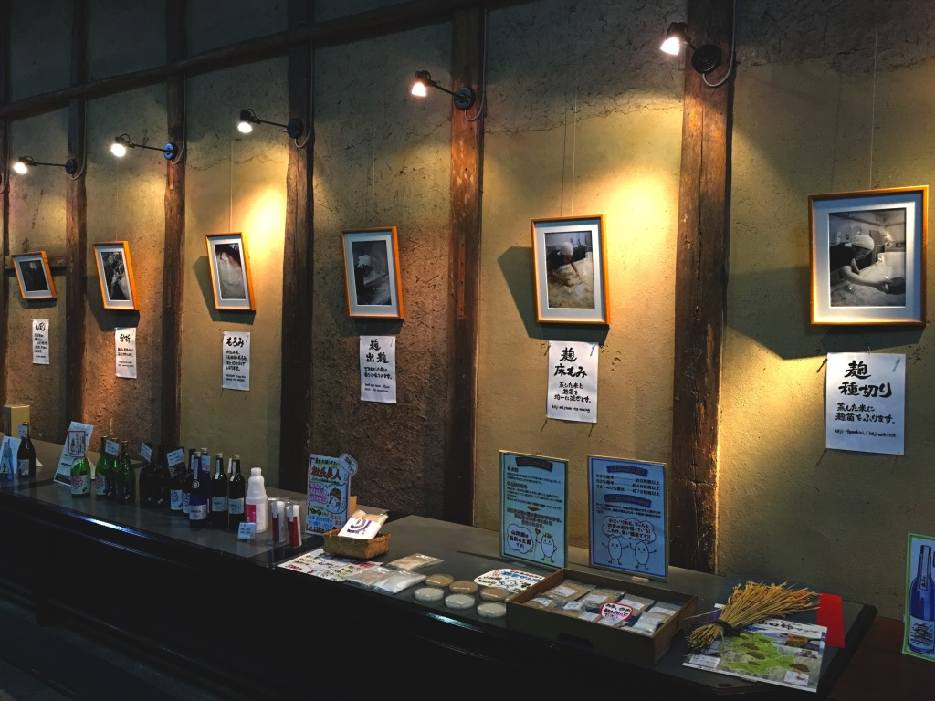 A wall delineating the history of Nadagiku Sake Brewery, with sake products lining in a row on the tables below.