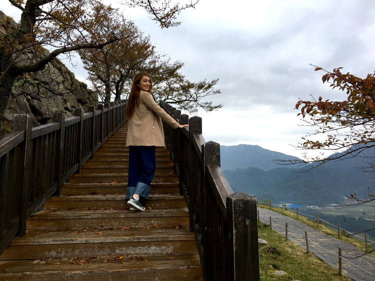 Me climbing up the wooden stairs along the castle ruins.